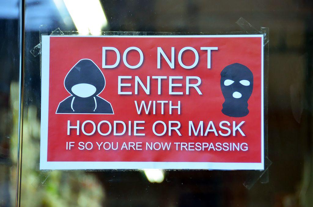 Табличка, запрещающая вход в магазин в худи и масках. История толстовки с капюшоном в статье по ссылке